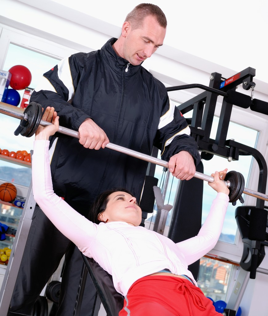 .man assisting woman weitght lifting at a gym